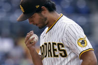 San Diego Padres starting pitcher Yu Darvish blows on his hand while warming up during the third inning of the team's baseball game against the Pittsburgh Pirates Wednesday, May 5, 2021, in San Diego. (AP Photo/Gregory Bull)