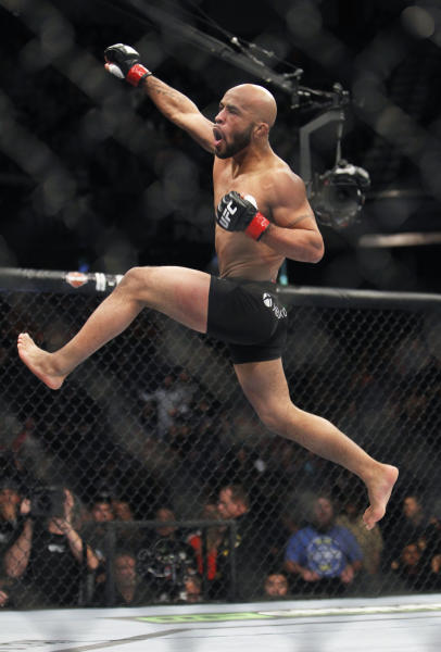 Defending champ Demetrious Johnson celebrates after knocking out Joseph Benavidez in the first round of their UFC flyweight mixed martial arts title fight in Sacramento, Calif., Saturday, Dec. 14, 2013. (AP Photo/Steve Yeater)