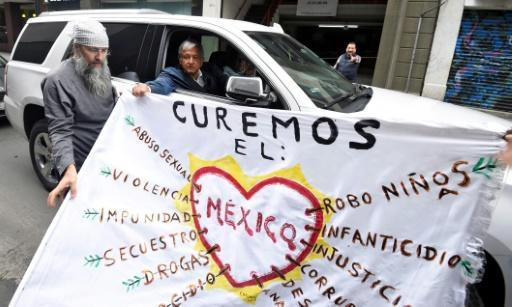 "Mexico's presidential candidate, Andres Manuel Lopez Obrador (in car), who leads most opinion polls, holds with a supporter a sign reading ""Let's cure Mexico"""