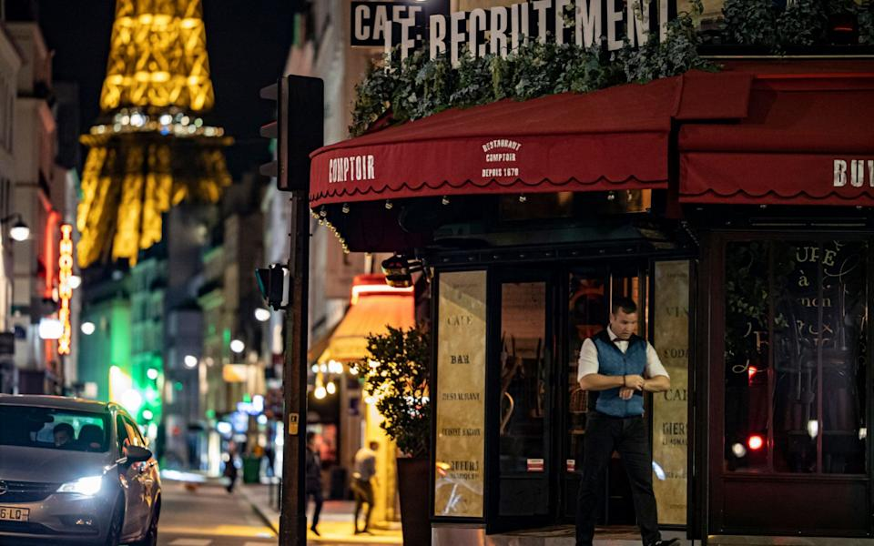A barman closes his establishment at 9pm as part of a city-wide night time curfew in Paris - Shutterstock