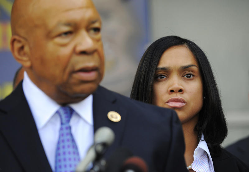 FILE - In this Aug. 3, 2015, file photo, State's Attorney Marilyn Mosby, right, listens as U.S. Rep. Elijah Cummings speaks during an announcement of the start of the Baltimore Federal Homicide Task Force, in Baltimore. Mosby is not the only Baltimore resident who relied on Cummings for advice. The congressman and civil rights advocate, who died Thursday, Oct. 17, 2019, at 68, mentored countless young people, faith leaders, activists, politicians and others throughout the years. (Lloyd Fox/The Baltimore Sun via AP, File)