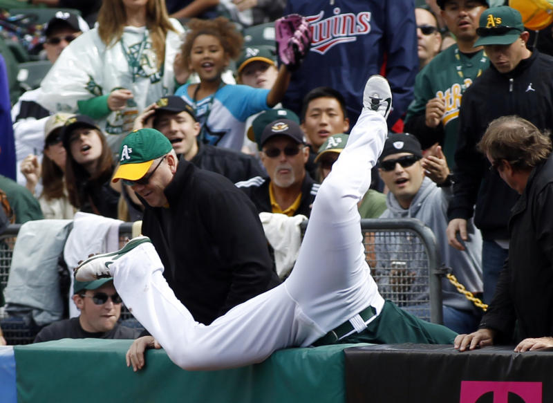 Oakland Athletics' Daric Barton falls over the ball as he unsuccessfully tries for a foul ball during the first inning of a baseball game against the Minnesota Twins, Saturday, Sept. 21, 2013, in Oakland, Calif. (AP Photo/George Nikitin)