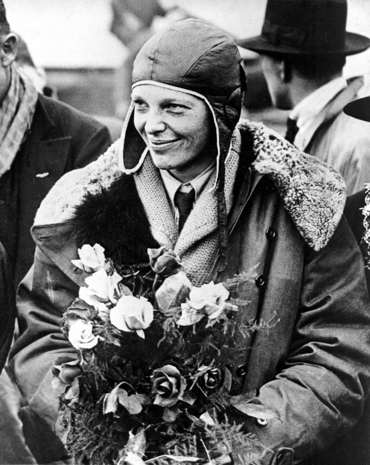 """American aviatrix Amelia Earhart poses with flowers as she arrives in Southampton, England, after her transatlantic flight on the """"Friendship"""" from Burry Point, Wales, on June 26, 1928.  The tri-motor """"Friendship"""" was piloted by two men as Earhart served as the commander, making her the first woman passenger to fly across the Atlantic.  (AP Photo)"""