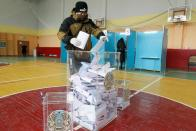 A man wearing a face mask and gloves to protect himself against coronavirus, casts his ballot at a polling station during a parliamentary elections in Nur-Sultan, the capital city of Kazakhstan, Sunday, Jan. 10, 2021. (AP Photo)