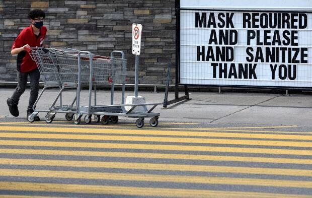 A staff member wears a mask as he collects carts at a store in Ottawa earlier this month. (Justin Tang/Canadian Press - image credit)