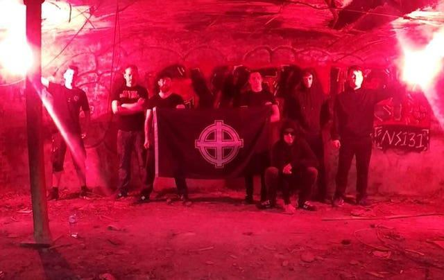 Benjamin Hannam, second right, posing with men holding a Celtic Cross flag (Metropolitan Police/PA)