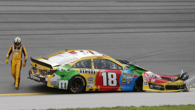 Driver Kyle Busch (18) walks around his wrecked race car during a NASCAR Sprint Cup series auto race at Kansas Speedway in Kansas City, Kan., Sunday, Oct. 6, 2013. (AP Photo/Orlin Wagner)