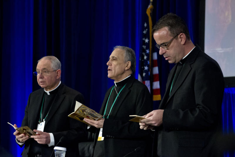 From left, Jose Gomez, archbishop of Los Angeles, Cardinal Daniel DiNardo of the Archdiocese of Galveston-Houston, president of the United States Conference of Catholic Bishops and Rev. J. Brian Bransfield, participates in a morning prayer, during the United States Conference of Catholic Bishops (USCCB), 2019 Spring meetings in Baltimore, Tuesday, Jun 11, 2019. (AP Photo/Jose Luis Magana)