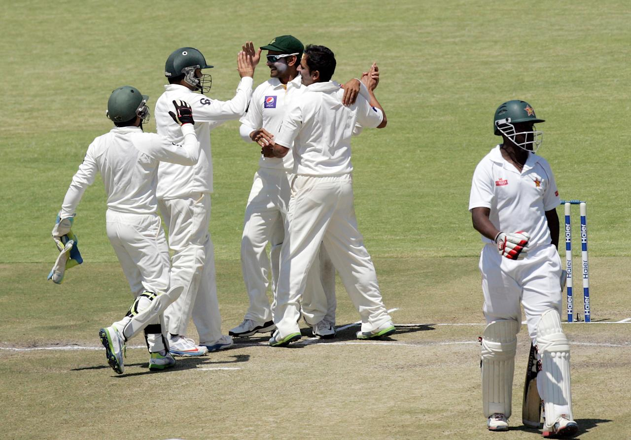 Pakistan's players celebrate after taking the wicket of Zimbabwe's Elton Chigumbura (R) on the fifth day of the first test match between Pakistan and Zimbabwe at the Harare Sports Club on September 7, 2013. AFP PHOTO / JEKESAI NJIKIZANA        (Photo credit should read JEKESAI NJIKIZANA/AFP/Getty Images)