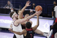 Gonzaga forward Drew Timme, left, and Loyola Marymount forward Keli Leaupepe, rear, and guard Joe Quintana (2) go after a rebound during the first half of an NCAA college basketball game in Spokane, Wash., Saturday, Feb. 27, 2021. (AP Photo/Young Kwak)