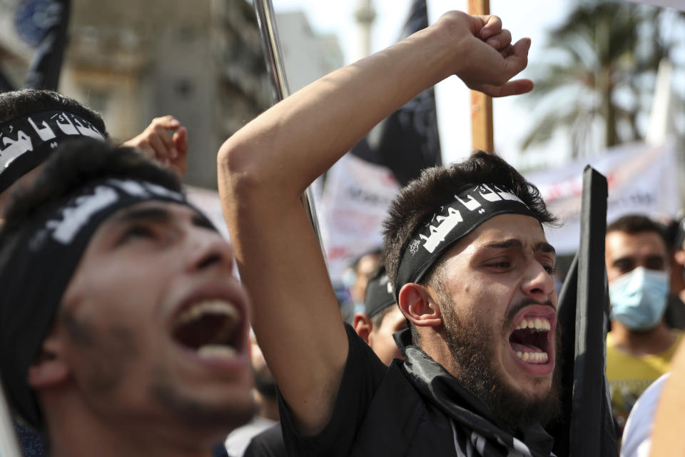 "FILE - In this Oct.30 2020 file photo, protesters chant slogans as they wear headbands with Arabic that read: ""We are your soldiers, Oh Muhammad,"" during a protest against French President Macron's comments over Prophet Muhammad caricatures, near the Pine Palace, which is the residence of the French ambassador, in Beirut, Lebanon. A spotlight of suspicion encircled Muslims again even before the latest acts of extremist violence, including two beheadings. French President Emmanuel Macron has forged ahead with a plan to rid Islam in France of extremists, part a project he labels ""separatism,"" a term that makes some Muslims wince. (AP Photo/Bilal Hussein, File)"