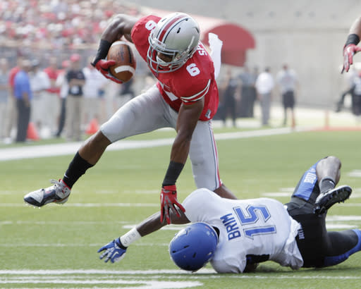 Ohio State wide receiver Evan Spencer, left, tries to jump over Buffalo defensive back Derek Brim during the first quarter of an NCAA college football game Saturday, Aug. 31, 2013, in Columbus, Ohio. Ohio State beat Buffalo 40-20. (AP Photo/Jay LaPrete)