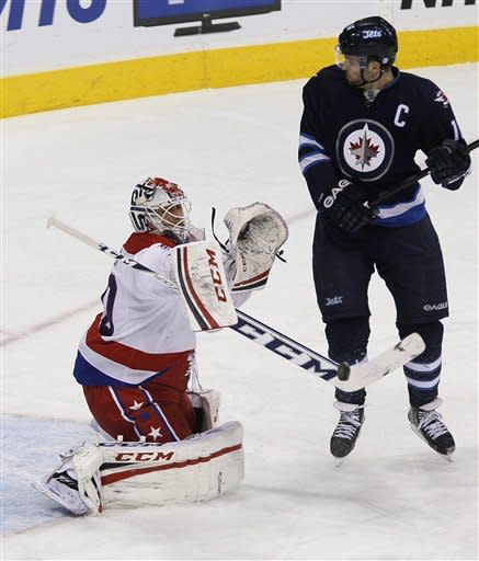 Washington Capitals goaltender Braden Holtby makes a save on a deflection by Winnipeg Jets Andrew Ladd during the first period of an NHL hockey game in Winnipeg, Manitoba, on Thursday, March 21, 2013. (AP Photo/The Canadian Press, John Woods)