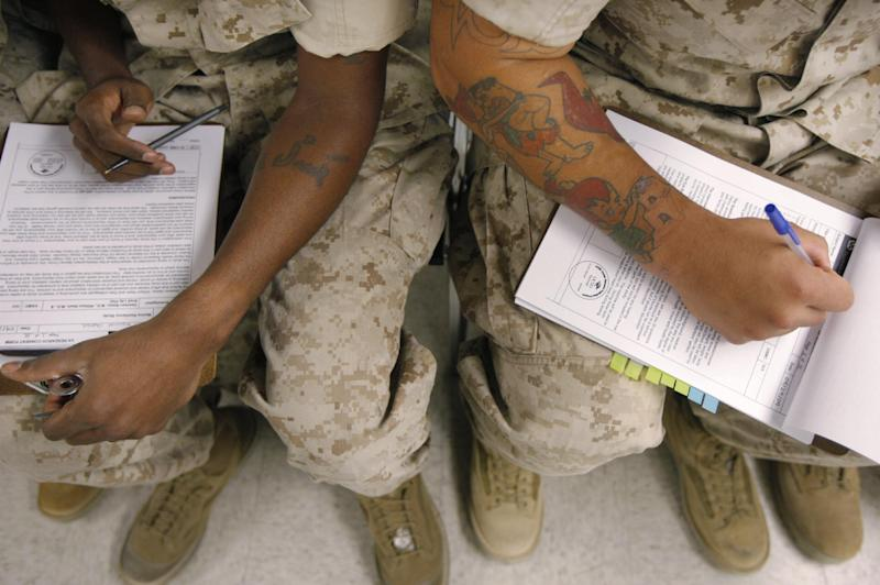 In this Sept. 29, 2009 file photo, U.S. Marines fill out research consent forms before taking psychological tests at the Marine Corps Air Ground Combat Center in Twentynine Palms, Calif. in a program testing hundreds of Marines and soldiers before they ship out to search for clues that might help predict who is most susceptible to post-traumatic stress disorder. The U.S. Institute of Medicine recommended on Friday, July 13, 2012 that soldiers returning from Iraq and Afghanistan be screened for post-traumatic stress disorder at least once a year and that federal agencies conduct more research to determine how well the various treatments for PTSD are working. (AP Photo/Jae C. Hong)