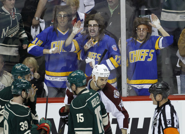 "FILE - In this April 21, 2014, file photo, fans dressed as the Hanson Brothers from the movie ""Slap Shot"" yell at players and referees as Minnesota Wild defenseman Clayton Stoner and Colorado Avalanche center Brad Malone are assessed penalties during the first period of Game 3 of an NHL hockey first-round playoff series in St. Paul, Minn. ""Slap Shot"" was No. 5 in The Associated Press' Top 25 favorite sports movies poll. (AP Photo/Ann Heisenfelt, File)"