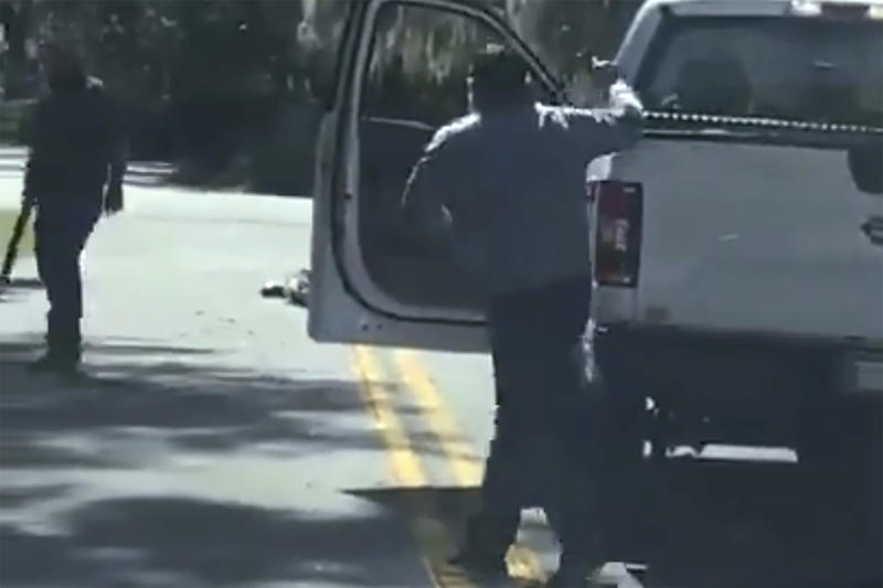 ADDS THAT THE AP HAS NOT BEEN ABLE TO VERIFY THE SOURCE OF THE VIDEO - This image from video posted on Twitter Tuesday, May 5, 2020, purports to show Ahmaud Arbery lying on the road after being shot as Travis McMichael, left, holding a shotgun, and his father, Gregory McMichael, holding a handgun, approach him in a neighborhood outside Brunswick, Ga., on Feb. 23, 2020. The AP has not been able to verify the source of the video. (Twitter via AP)