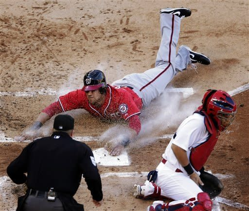 Washington Nationals' Ian Desmond slides home pas St. Louis Cardinals catcher Yadier Molina to score on a single by Jordan Zimmermann during the second inning of Game 2 of the National League division baseball series, Monday, Oct. 8, 2012, in St. Louis. (AP Photo/Charlie Riedel)