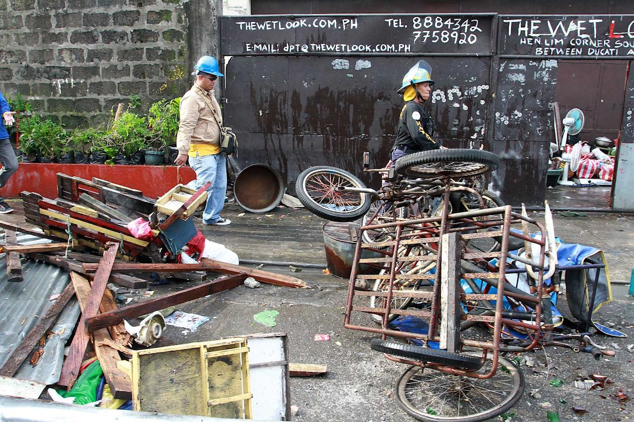 Informal settlers and government demolition crew face off during a demolition operation at Guatemala Street, Barangay San Isidro in Makati City, south of Manila, on 24 September 2012. Around 300 families occupying an 800-meter government property defended their homes from the demolition team and police, throwing rocks and bottles. A local radio reported at least six policemen and a media worker were injured in the violent demolition as of presstime. (Voltaire Domingo/NPPA Images)