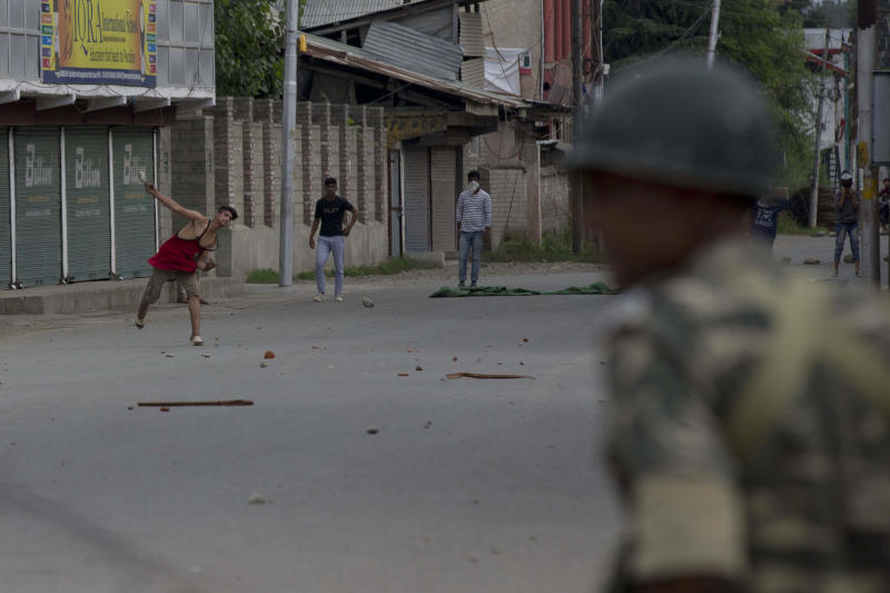 Kashmiri Muslim protesters throw stones at Indian paramilitary soldiers during curfew like restrictions in Srinagar, India, Friday, Aug. 16, 2019. Hundreds of Kashmiris held a street protest in the Indian-controlled Kashmir even as India's government assured the Supreme Court on Friday that the situation in disputed Kashmir is being reviewed daily and unprecedented security restrictions will be removed over the next few days, an attorney said after the court heard challenges to India's moves. (AP Photo/Dar Yasin)