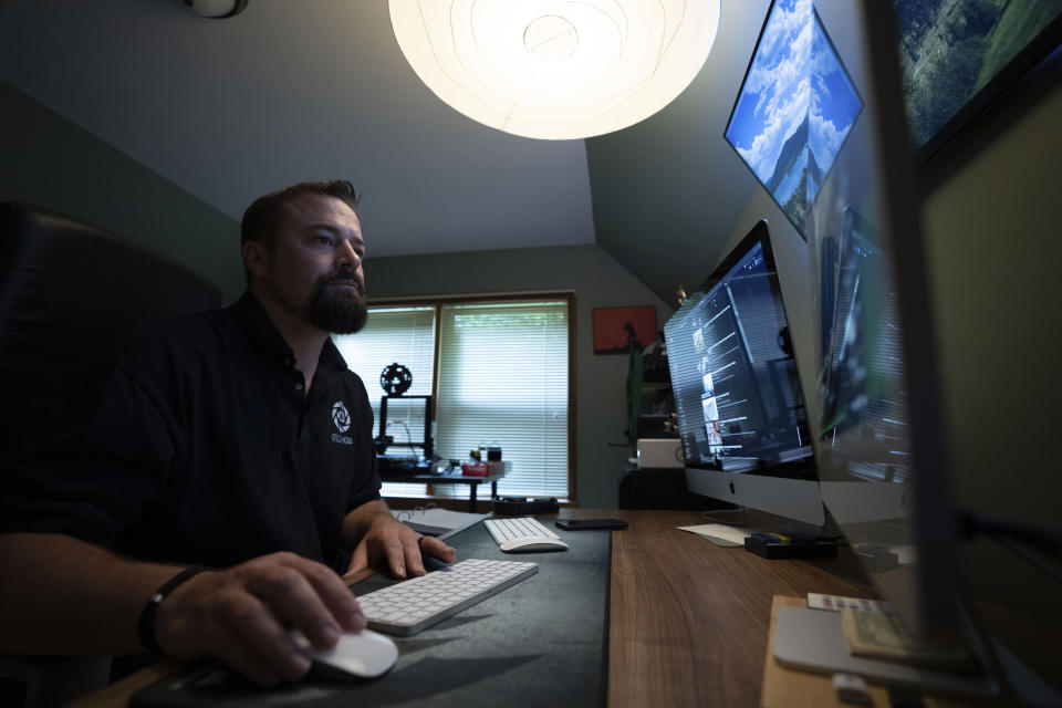 Korey Rowe edits video in his video production office at his home in Oneonta, N.Y., on Thursday, Aug. 12, 2021. Twenty years on, the skepticism and suspicion first revealed by 9/11 conspiracy theories has metastasized, spread by the internet and nurtured by pundits and politicians like Donald Trump. One hoax after another has emerged, each more bizarre than the last: birtherism. Pizzagate. QAnon. (AP Photo/Robert Bumsted)