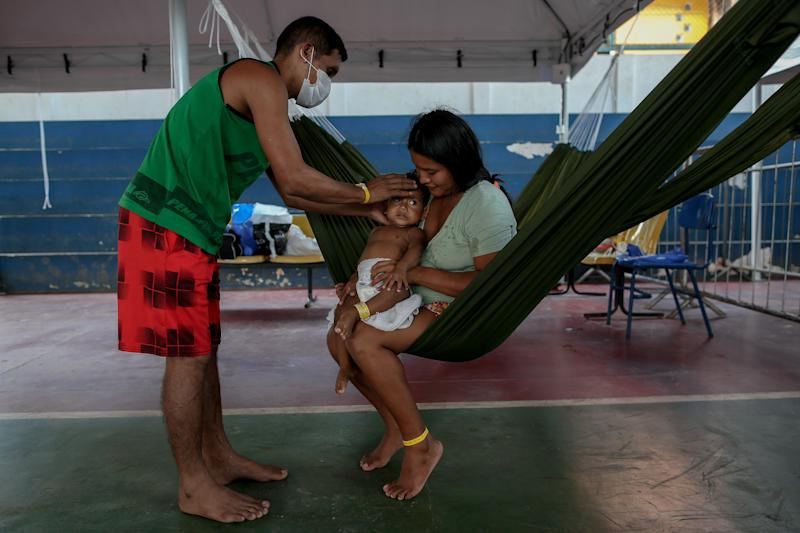 A couple and their child of the Warao tribe, Venezuela's second-largest indigenous group, suffering from symptoms of the novel coronavirus, wait for medical care from Doctors Without Borders in Manaus, Amazonas state, Brazil, on June 3, 2020. (Photo by MICHAEL DANTAS / AFP) (Photo by MICHAEL DANTAS/AFP via Getty Images)