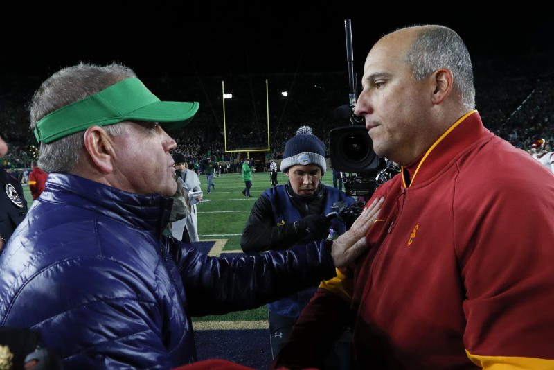Notre Dame head coach Brian Kelly, left, and Southern California head coach Clay Helton meet after an NCAA college football game in South Bend, Ind., Saturday, Oct. 12, 2019. (AP Photo/Paul Sancya)
