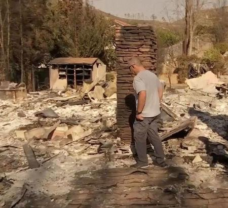 Ventura Sheriff Commander Dave Murray walks through his destroyed property after his house was reduced to ashes in Ventura, California, U.S. December 8, 2017. Picture taken December 8, 2017. REUTERS/Ben Gruber