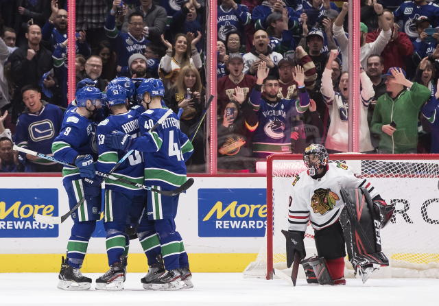Vancouver Canucks' J.T. Miller, Bo Horvat, Brandon Sutter and Elias Pettersson, from left, celebrate Horvat's goal against Chicago Blackhawks goalie Corey Crawford during the first period of an NHL hockey game Wednesday, Feb. 12, 2020, in Vancouver, British Columbia. (Darryl Dyck/The Canadian Press via AP)