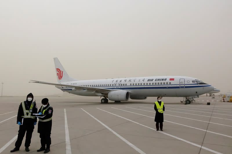 Staff members stand on the tarmac of Beijing Capital International Airport as the city is hit by a sandstorm, in Beijing