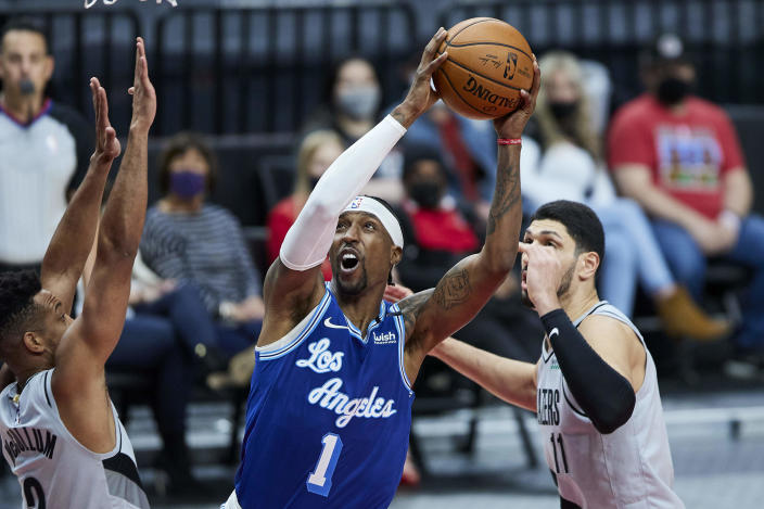Los Angeles Lakers guard Kentavious Caldwell-Pope, center, shoots between Portland Trail Blazers guard CJ McCollum, left, and center Enes Kanter during the first half of an NBA basketball game in Portland, Ore., Friday, May 7, 2021. (AP Photo/Craig Mitchelldyer)