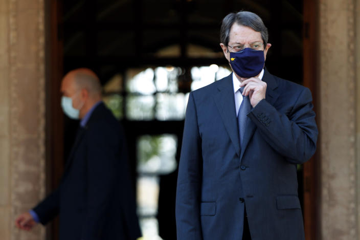 Cyprus President Nicos Anastasiades adjusts his health mask as wait the European Union Council President Charles Michel at the entrance of the Presidential Palace in the capital Nicosia, Cyprus, Wednesday, Sept. 16, 2020. Michel is visiting Cyprus after traveling to Greece amid a diplomatic drive to de-escalate a weeks-long standoff at sea over Turkey's hydrocarbons search in waters where Greece and Cyprus claim exclusive economic rights. (AP Photo/Petros Karadjias)