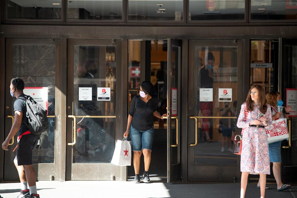 NEW YORK, NEW YORK - JUNE 24: A woman walks out of Macy's Herald Square with a shopping bag as the city moves into Phase 2 of re-opening following restrictions imposed to curb the coronavirus pandemic on June 24, 2020 in New York City. Phase 2 permits the reopening of offices, in-store retail, outdoor dining, barbers and beauty parlors and numerous other businesses. New York state plans on re-opening in four phases. (Photo by Alexi Rosenfeld/Getty Images)