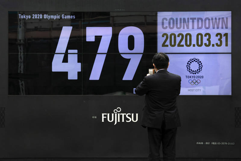 A man takes pictures of a countdown display for the Tokyo 2020 Olympics and Paralympics Tuesday, March 31, 2020, in Tokyo.  The countdown clock is ticking again for the Tokyo Olympics. They will be July 23 to Aug. 8, 2021. The clock read 479 days to go. This seems light years away, but also small and insignificant compared to the worldwide fallout from the coronavirus. (AP Photo/Jae C. Hong)