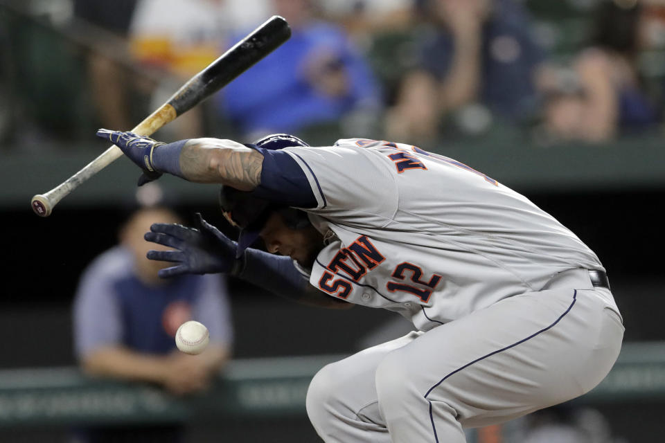 Houston Astros' Martin Maldonado ducks out of the way of a pitch from Baltimore Orioles reliever Tayler Scott during the seventh inning of a baseball game Saturday, Aug. 10, 2019, in Baltimore. Maldonado's bat made contact with the ball and it rolled into fair territory; Scott threw him out at first base. (AP Photo/Julio Cortez)