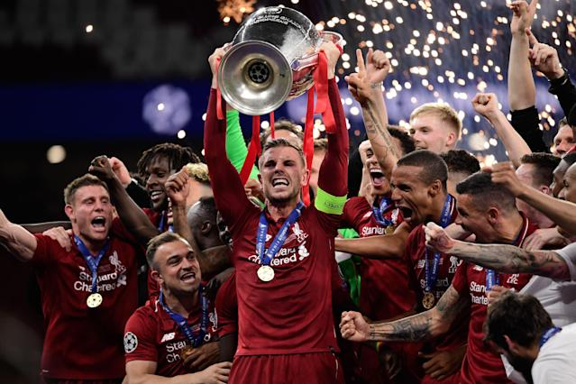 Liverpool's English midfielder Jordan Henderson (C) raises the trophy (Photo by JAVIER SORIANO / AFP)