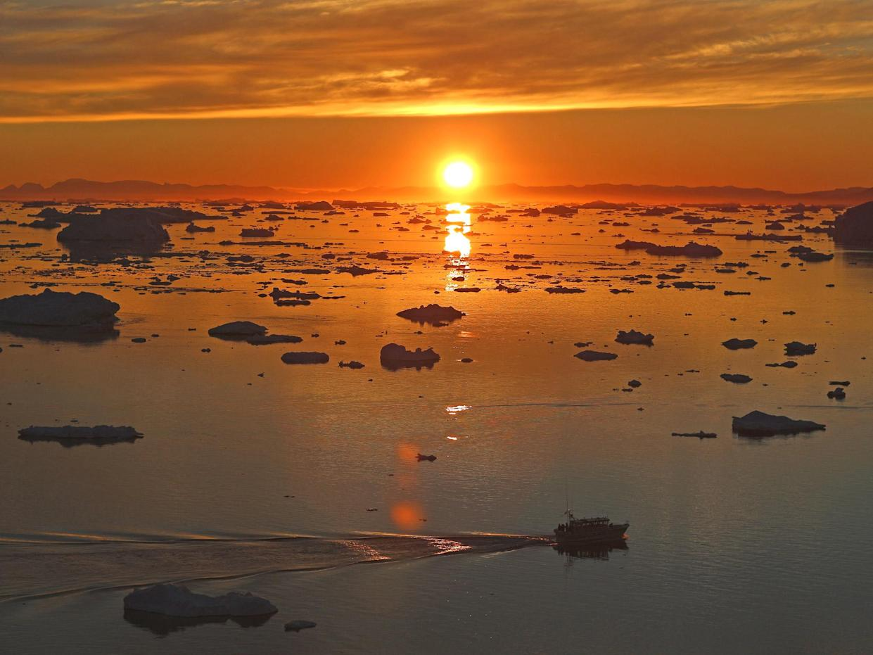 The sun sets over icebergs near Ilulissat in Greenland: Getty Images