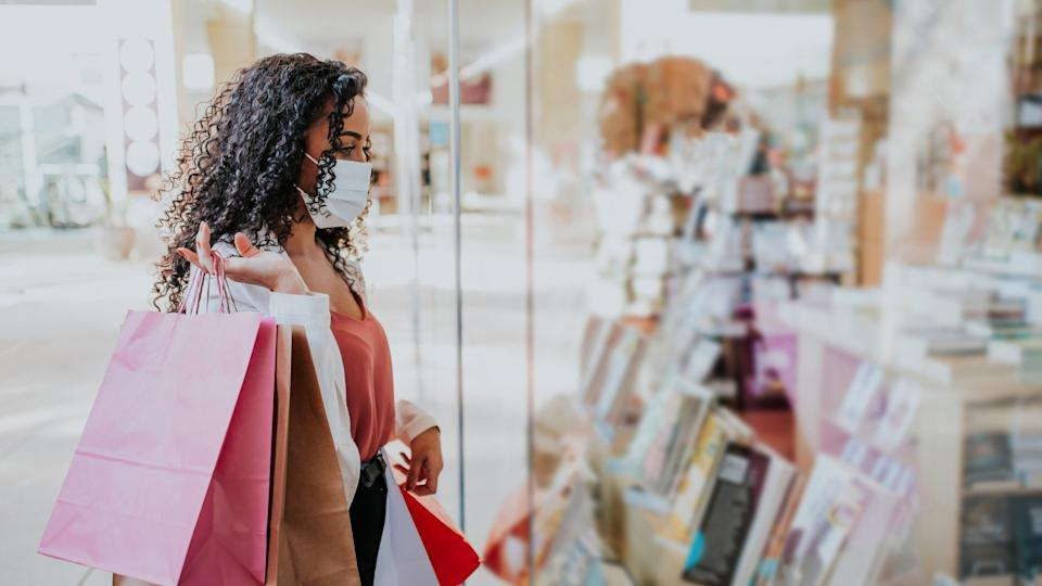 Woman in shopping mall with bags shopping during pandemic and wearing face mask against coronavirus.