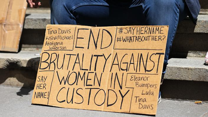 A person holds a sign at the #whatabouther rally for women being held at Riker's Island in front of the New York Stock exchange on April 26, 2021 in New York City. (Michael M. Santiago/Getty Images)