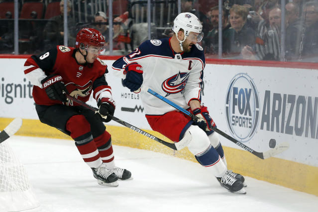 Columbus Blue Jackets left wing Nick Foligno, right, shields Arizona Coyotes center Clayton Keller (9) from the puck in the first period during an NHL hockey game, Thursday, Nov. 7, 2019, in Glendale, Ariz. (AP Photo/Rick Scuteri)