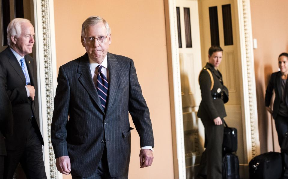 Senate Majority Leader Mitch McConnell arrives to a weekly press conference on Capitol Hill.