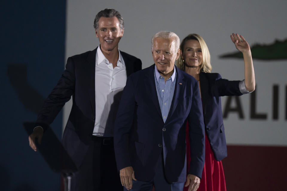 President Joe Biden, center, smiles to the crowd as he is flanked by California Gov. Gavin Newsom, and wife, Jennifer Siebel Newsom, at a rally ahead of the California gubernatorial recall election Monday, Sept. 13, 2021, in Long Beach, Calif. (AP Photo/Jae C. Hong)