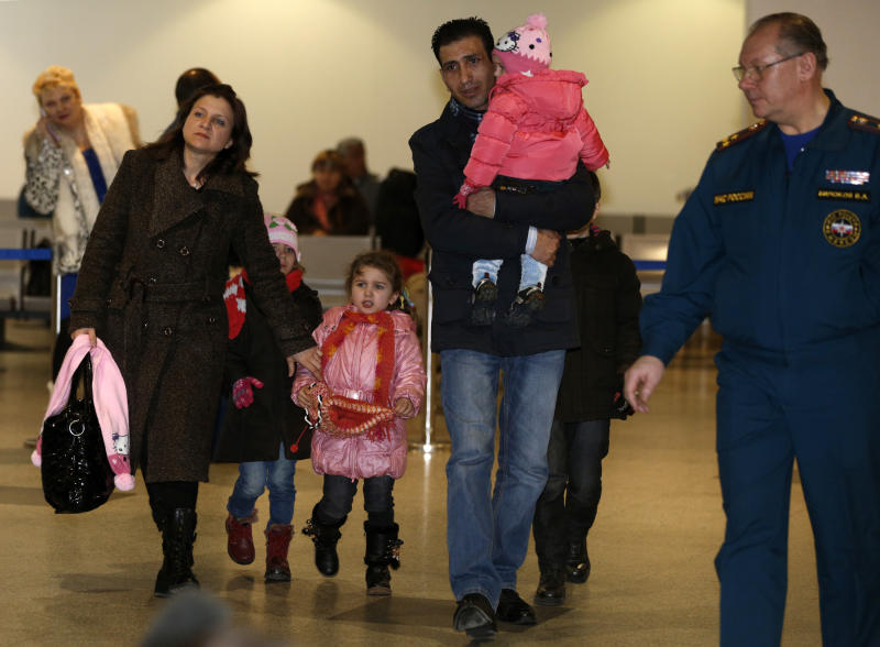 A Russian-Syrian family leave passport control zone just after their arrival from Beirut in Moscow Domodedovo airport , Russia, Wednesday, Jan. 23, 2013. The Kremlin's evacuation of Russians from Syria on Tuesday marks a turning point in its view of the civil war, representing increasing doubts about Bashar Assad's hold on power and a sober understanding that it has to start rescue efforts before it becomes too late. The operation has been relatively small-scale - involving fewer than 100 people, mostly women and children - but it marks the beginning of what could soon turn into a risky and challenging operation.  (AP Photo/Alexander Zemlianichenko)
