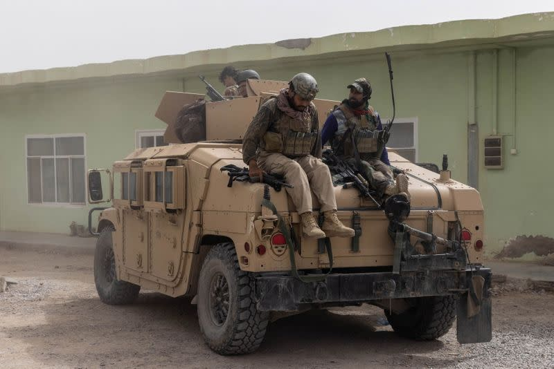 Members of Afghan Special Forces climb down from a humvee as they arrive at their base after heavy clashes with Taliban during the rescue mission of a police officer besieged at a check post, in Kandahar province