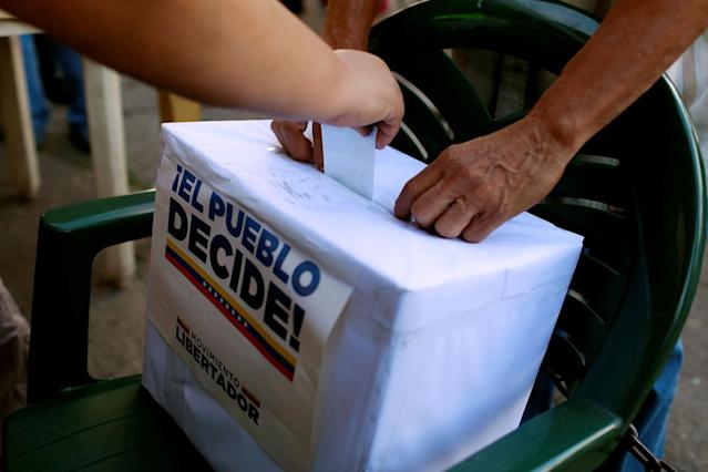 "<p>People cast their votes during an unofficial plebiscite against Venezuela's President Nicolas Maduro's government and his plan to rewrite the constitution, in Caracas, Venezuela July 16, 2017. The writing on the box reads ""The people decide, Liberator Movement."" (Marco Bello/Reuters) </p>"