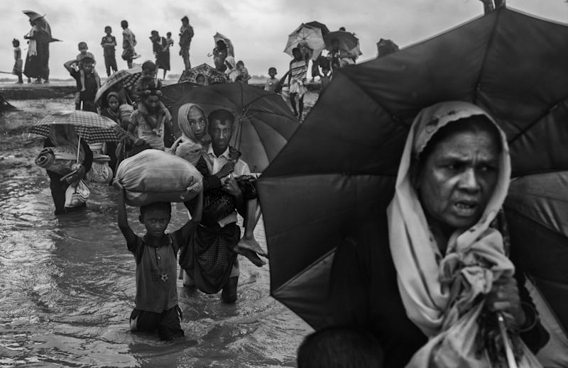 Rohingya refugees carry their belongings as they walk through water on the Bangladesh side of the Naf River after fleeing their village in Myanmar.