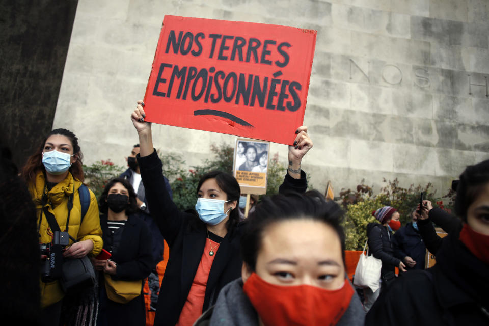 An activist holds a placard reading « Our poisoned lands » during a gathering in support of people exposed to Agent Orange during the Vietnam War, in Paris, Saturday Jan. 30, 2021. Activists gathered Saturday in Paris in support of people exposed to Agent Orange during the Vietnam War, after a French court examined a case opposing a French-Vietnamese woman to 14 companies that produced and sold the toxic chemical. (AP Photo/Thibault Camus)