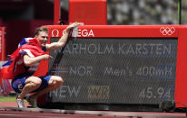 Karsten Warholm, of Norway celebrates next to the scoreboard showing his world record as he wins the gold medal in the final of the men's 400-meter hurdles at the 2020 Summer Olympics, Tuesday, Aug. 3, 2021, in Tokyo, Japan. (AP Photo/Martin Meissner)