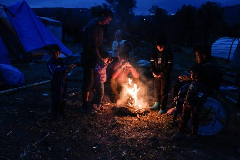 Migrants light a fire in their makeshift camp on Chios island