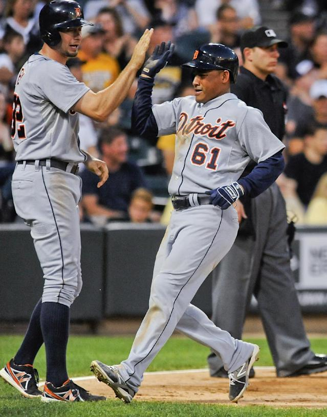 Detroit Tigers' Don Kelly, left, and Ezequiel Carrera score on a hit by Ian Kinsler in the fourth inning in the second game of a baseball doubleheader against the Chicago White Sox in Chicago on Saturday, Aug. 30, 2014. (AP Photo/Matt Marton)