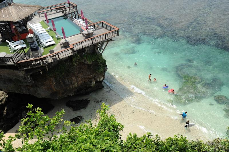 Tourists prepare to surf at Uluwatu beach South Kuta in Badung regency on Bali island.